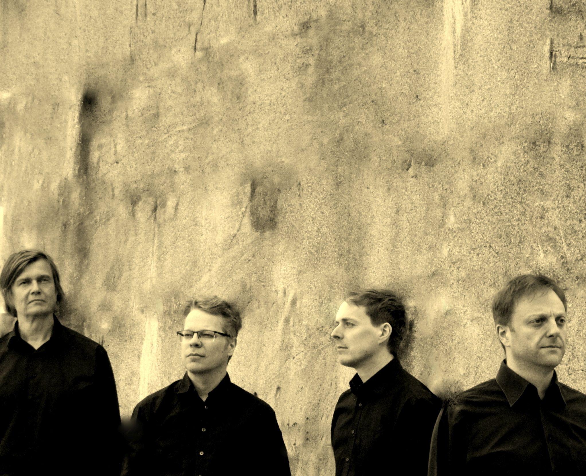 Kuvassa Kanto Ensemblen neljä jäsentä tummissa vaatteisa vaalea seinää vasten.
